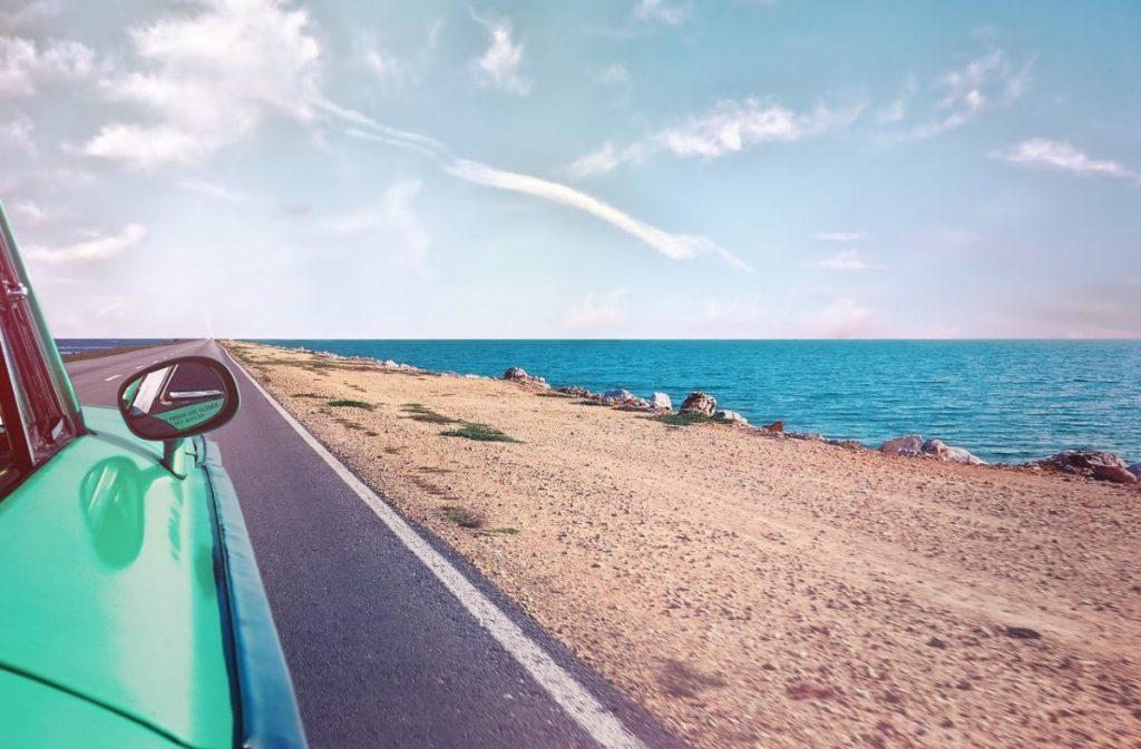 green-car-near-seashore-with-blue-ocean